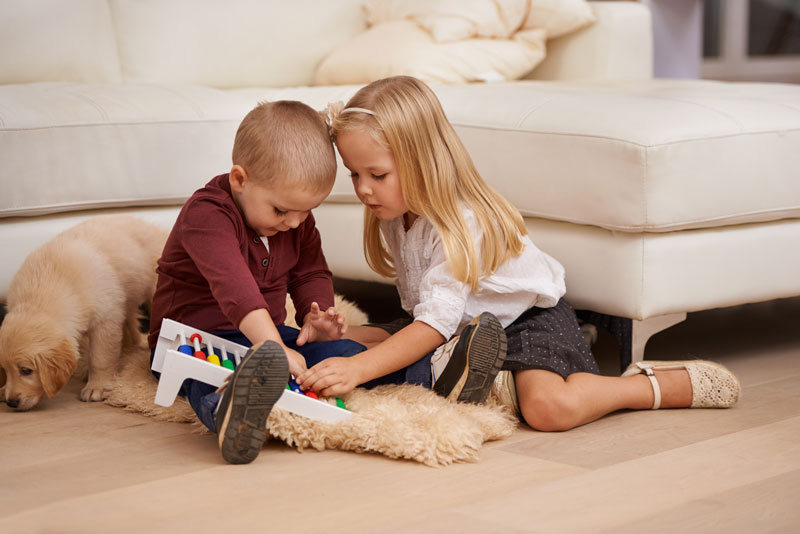 Young children playing with toy while sitting on floor