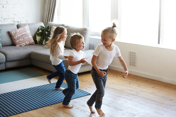 Three children playing in family room