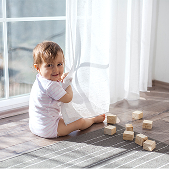 A young child playing with blocks on a wooden floor