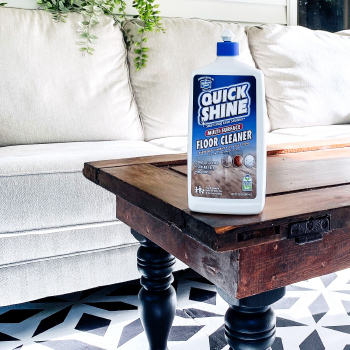 A bottle of Multi-Surface Floor Cleaner sitting on a wooden table