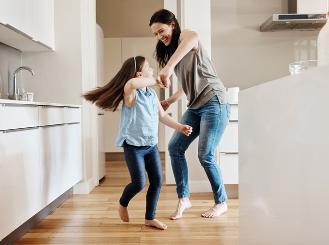 Woman and young girl dancing in kitchen