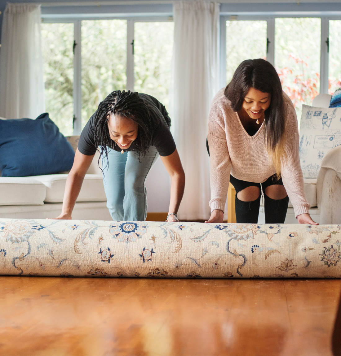 Two women rolling out an area rug