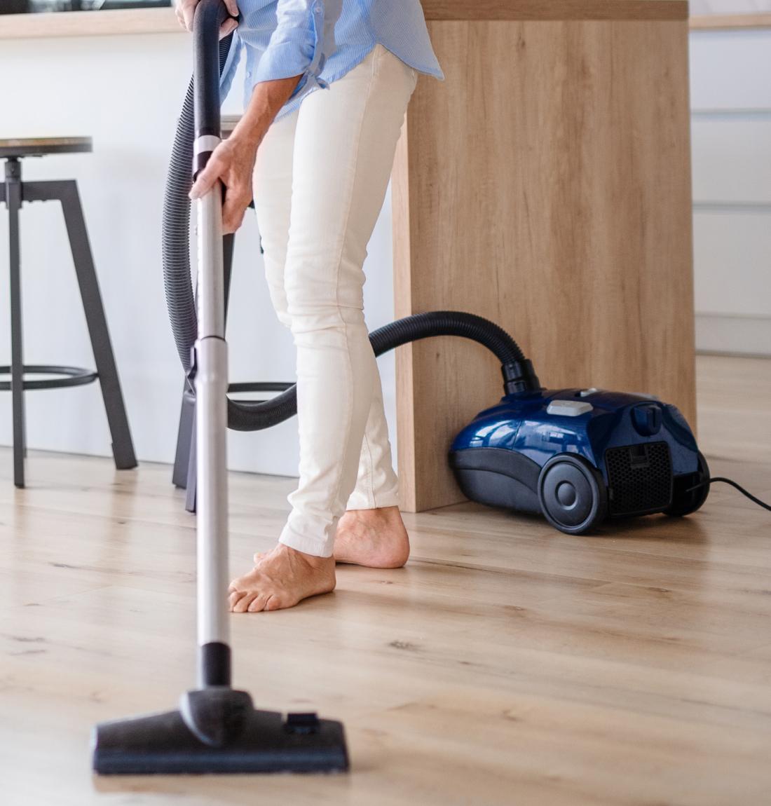 Woman vacuuming laminate floor