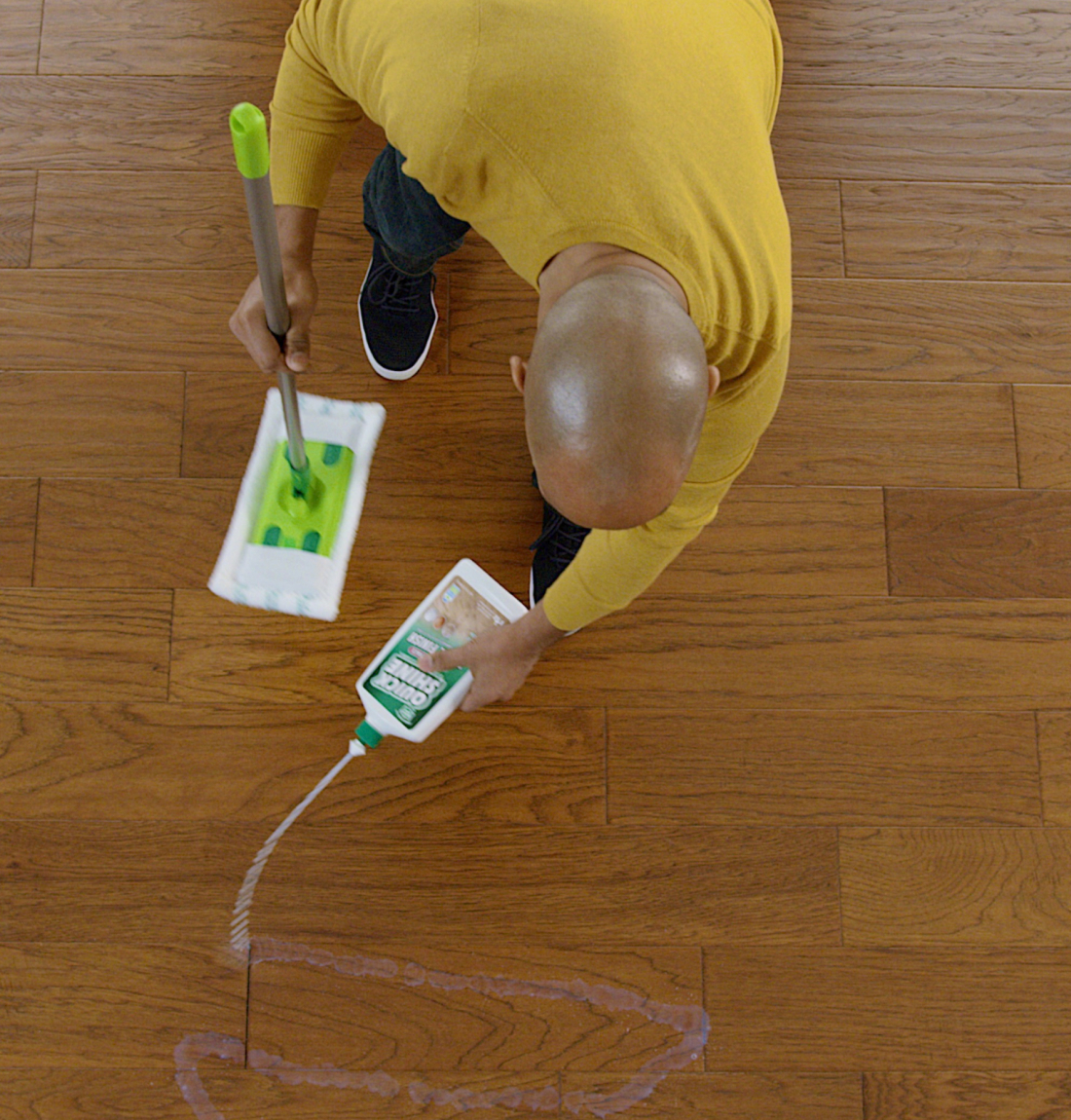 Man squirting Quick Shine® Multi-Surface Floor Finish on hardwood floor