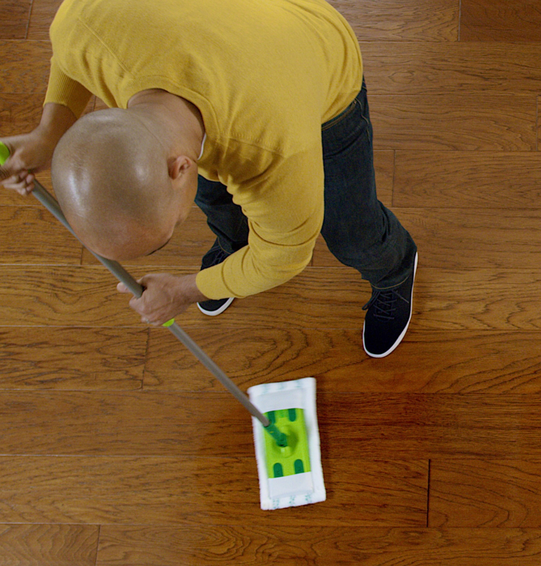 Man dry mopping hardwood floor