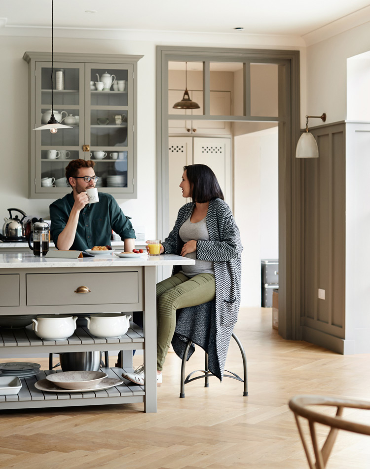 A couple sitting at kitchen island having breakfast