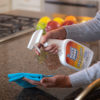 Woman spraying 3-in-1 Disinfectant Surface Cleaner onto microfiber cloth